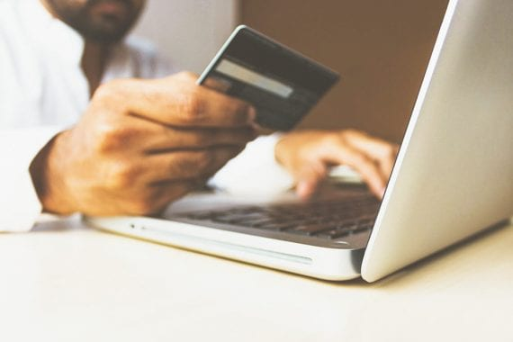 Image of a shopper holding a credit card by a laptop