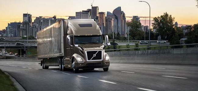Photo of a Volvo VNR semi-truck on a city highway.